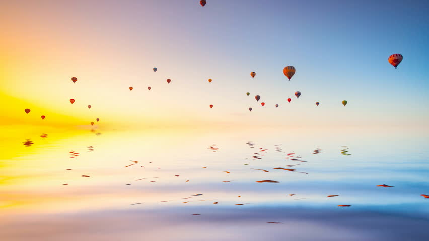 Hot air ballons reflected in ocean water fly in colorful sky at morning sunrise. Majestic summer landscape. Exploring beauty world, holidays and recreation. Travel background. Slow motion 4K footage