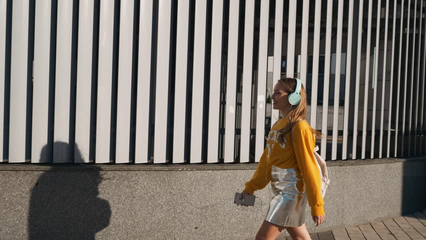 Portrait of young cute attractive young girl in urban background listening to music with headphones. Woman wearing yellow blouse and silver skirt. | Shutterstock HD Video #1013067581