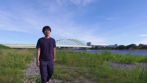 Young JAPANESE MAN walking and thinking of something at the riverside of Tama river in Tokyo.