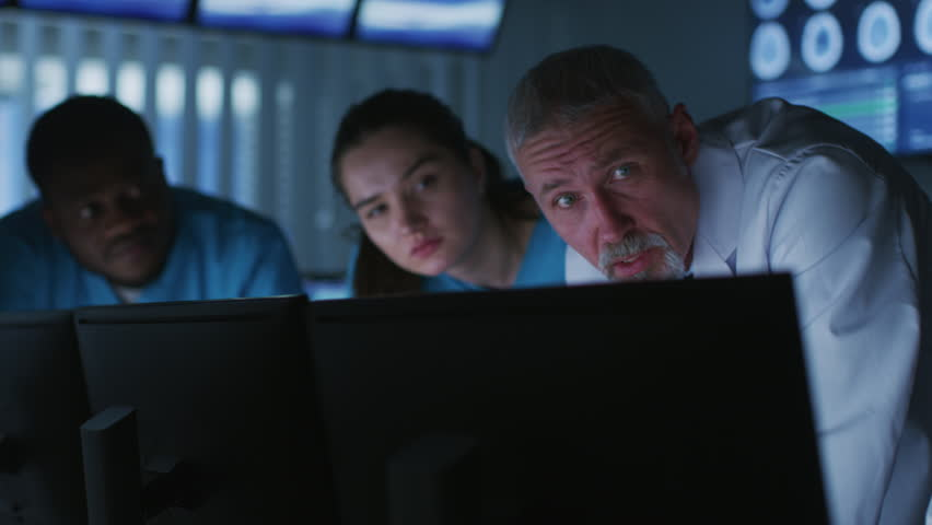 Diverse Group of Medical Scientists Solve Problems and Point at Computer Screens Showing CT, MRI Scans. Neurologists / Neuroscientists Working in Brain Research Laboratory. Shot on RED EPIC-W 8K.