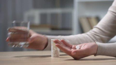 Woman taking pills against headache or menstrual pain, depression treatment