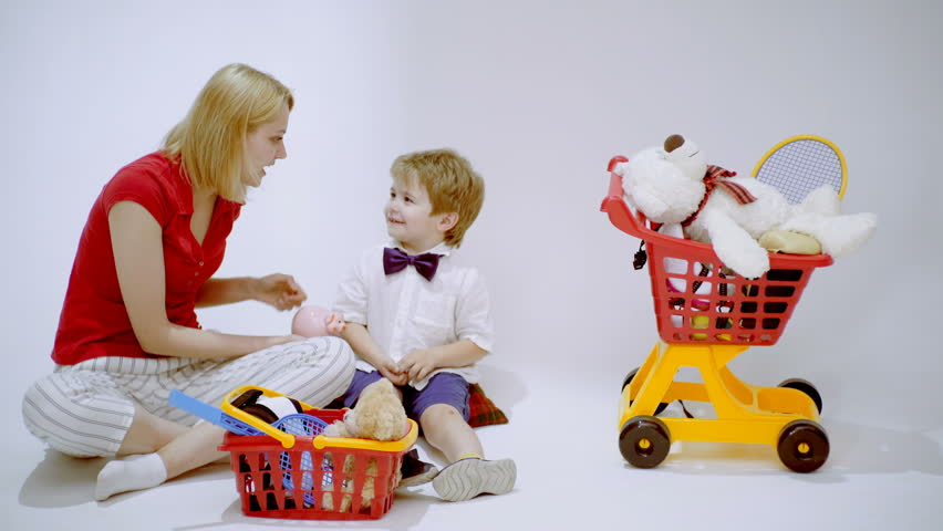 Mother teach her son to count money. smiling little boy plays shop with mom. Mother and son playing shopping