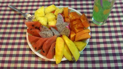 On the table is a plate of fruit. Female hand takes papaya with a fork