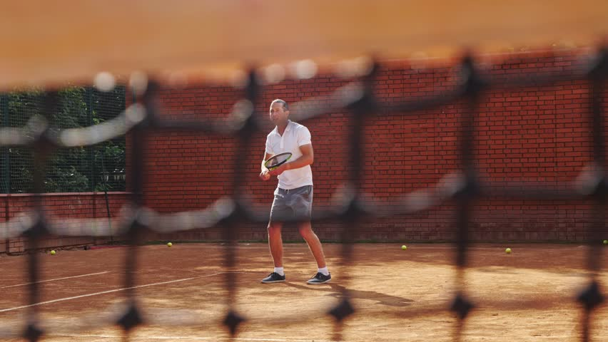 Young attractive man playing tennis on orange clay tennis court   Shutterstock HD Video #1013106941