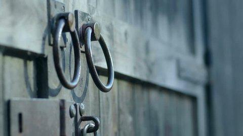 Close up of two barn door handles, hand reaches in and opens barn door