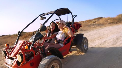 Two girlfriends extremely spend holidays driving quadricycle in slow motion. Active women driving buggy car. Young women controlling beach buggy. Courageous women. Extreme ride