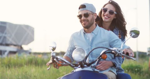 Portrait shot of the handsome young man riding a motorcycle and his pretty girlfriend sitting behind him and hugging. Blurred. Outdoors.