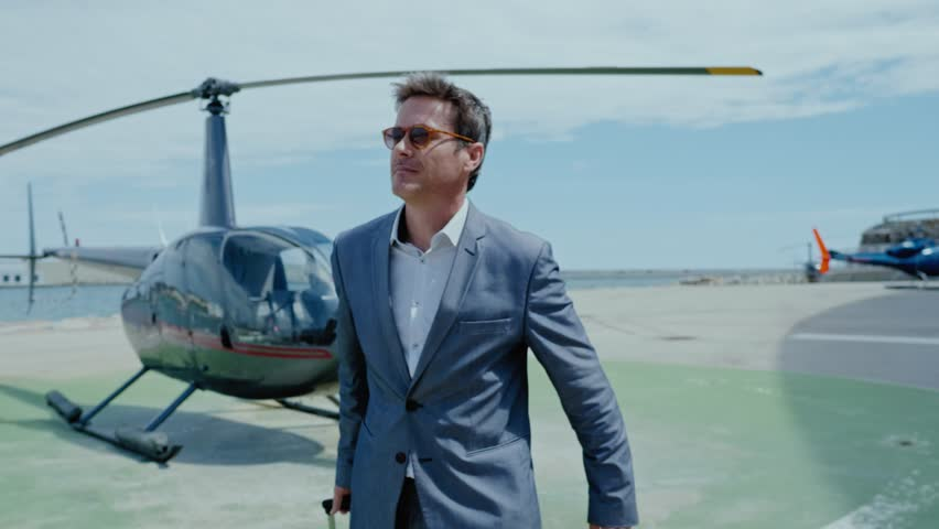 Businessman waiting near private helicopter