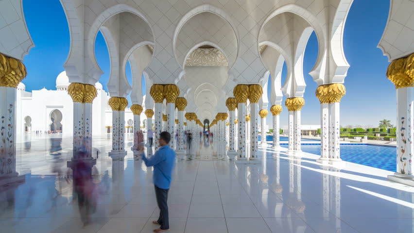 Sheikh Zayed Grand Mosque timelapse hyperlapse in Abu Dhabi, the capital city of United Arab Emirates. People walking between columns. Blue sky at sunny day