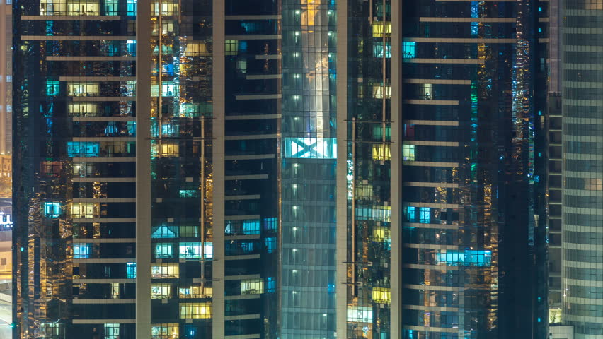 Windows of the multi-storey skyscrapers of glass and steel office lighting and people within timelapse. Blinking light in apartments. Abu Dhabi, UAE | Shutterstock HD Video #1013213471