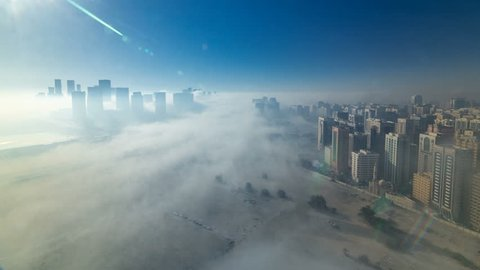 Skylines under the thick fog at the street timelapse of Abu Dhabi at morning, the biggest and most populated city of United Arab Emirates. Aerial view of skyscrapers from above after sunrise