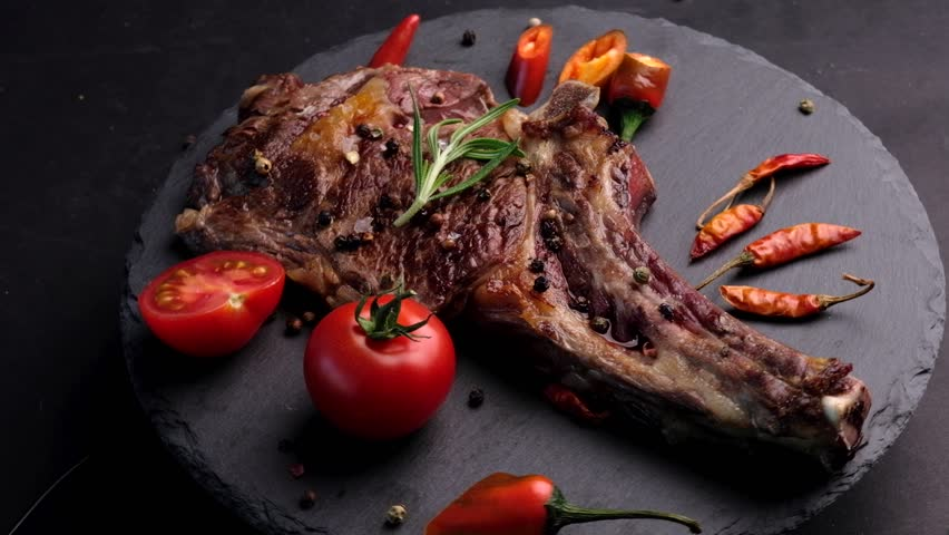 Grilled beef steak on bone with tomatoes rotating on the stone cutting board