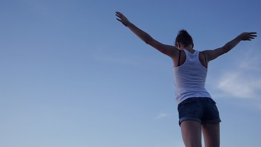 A slender attractive girl raised her arms up, waved them, she felt freedom, against the blue sky. HD, 1920x1080, slow motion. #1013248691