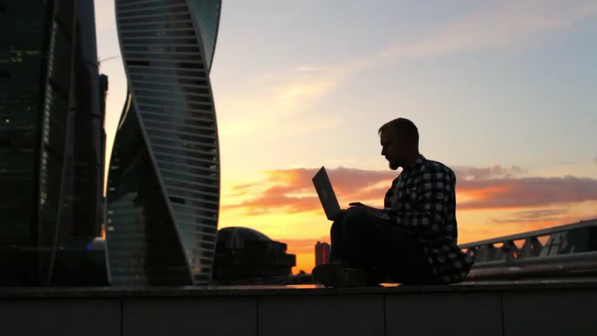 silhouette of a businessman hipster with a laptop on a background of skyscrapers and sunset #1013260901