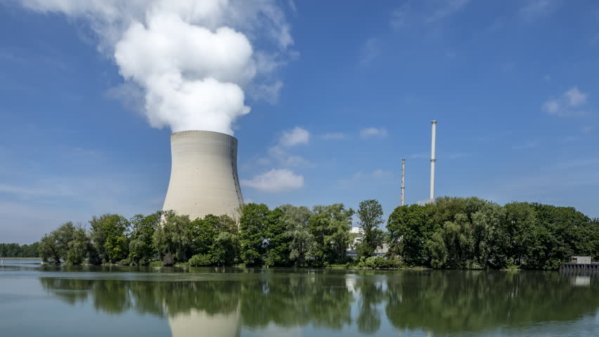 Time lapse long shot of a nuclear power station with funnel, reactor dome and huge cooling tower steaming on the far side of a wide river on a sunny spring day.