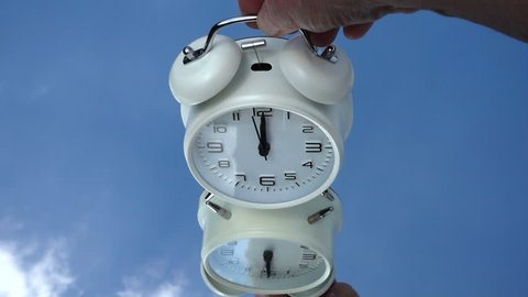 Time related concept: Slow motion close shot of a man's hand placing a traditional alarm clock on a mirrored surface against a blue sky, at exactly 12-o-clock, with the alarm hammer ringing the bells.