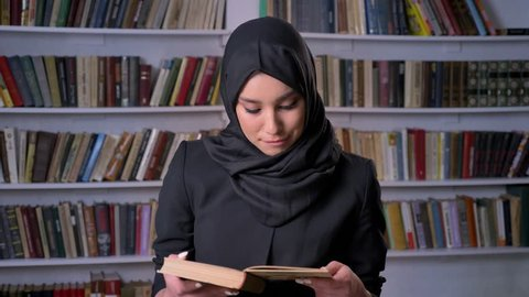 Young beautiful muslim girl in hijab is reading book, watching at camera, smiling, bookshelf on background, religious concept