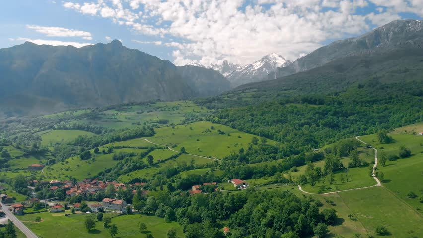Panoramic aerial view of green valley with Naranjo de Bulnes mountain peak on the background in the Picos de Europa national park in northern Spain