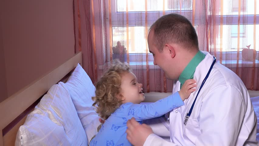Friendly doctor playing and embrace with three year old sick patient during visit. Static shot. 4K UHD