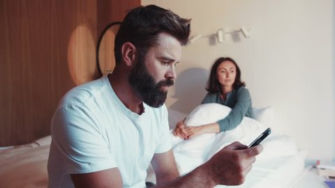 Sad bearded man in white shirt sits on the corner of the bed, using the smartphone, his unhappy wife sits on the background. Jealousy, conflict situation, no trust. Fighting, arguing.