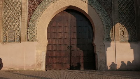 Camera tilt down view from top to bottom of Bab Mansour Gate wooden door in Meknes, Morocco