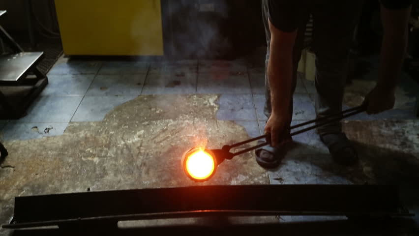 Molten silver being poured from a crucible into an ingot mold with the light coming from the molten silver. in the industrial workshop .
