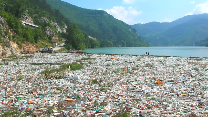 Plastic bottles in a polluted river water. Aerial view, drone view | Shutterstock HD Video #1013359631