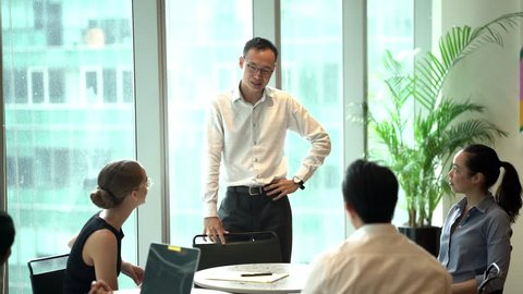 Portrait of a Chinese Asian man giving a business presentation and leading a discussion with his small but diverse team of colleagues. He is professionally dressed and speaking in an office.
