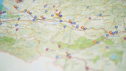 Hand pushing a red pin on a paper map, gas stations highlighted, Georgia (country), Kutaisi