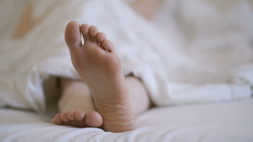 Woman in bare legs and feet on the bed