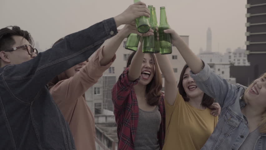 Slow motion - Group of young asian women and man people dancing and raising their arms up in air music played by dj at sunset urban party on rooftop. Young asian friends hanging out with drinks beer.