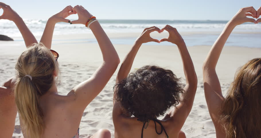 Group of friends on the beach making heart shaped gesture with their hands on summer vacation RED DRAGON