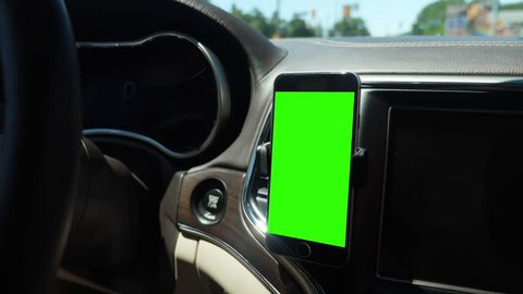 A handheld view of a driver's smartphone attached to a vent on the dashboard. Green screen with optional tracking points for advanced screen replacement.