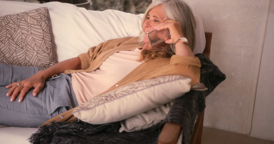 Fashionable senior woman lying on sofa and making call on mobile phone at home
