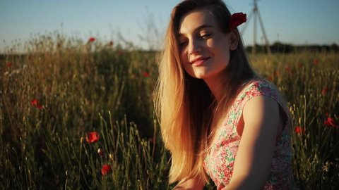 Cute young Ukrainian woman without makeup sitting among red flowers in field. Beautiful Caucasian girl with flower in hair touching poppies. Femininity. Natural beauty.