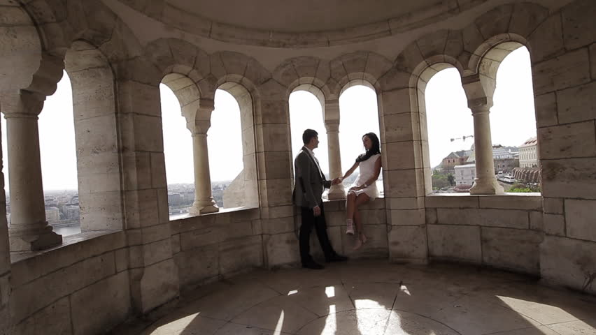 Young beautiful couple hold hands at the old walls of the Fishermen's Bastion in Budapest.   Shutterstock HD Video #1013468891