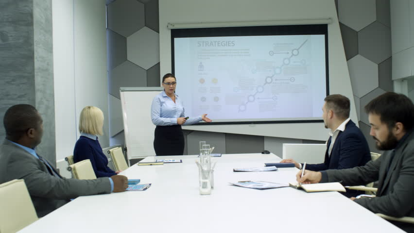 Businesswoman standing at whiteboard and explaining presentation to diverse team of coworkers sitting at meeting table | Shutterstock HD Video #1013469551
