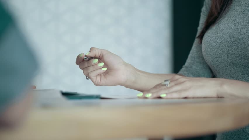 Close up european female hands with bright manicure thoughtfully holding pen paper on office desk creative business team meeting and brainstorming in modern start up office people group teamwork