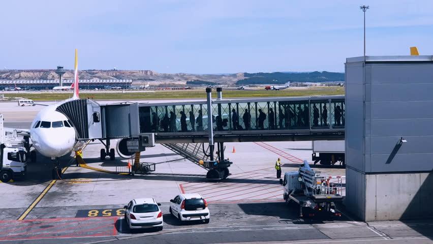 Airport passengers boarding on a plane, people walking through jet bridge. People walking in airport | Shutterstock HD Video #1013542721