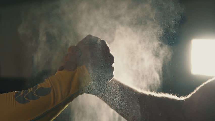Two athletes shaking hands in gym while their hands are covered in magnesia. Hands of gymnast clapping white chalk powder in slow motion. Cloud against dark background