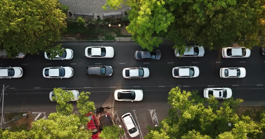 Aerial Drone Flight top down View of freeway busy city rush hour heavy traffic jam highway.  Aerial view of the vehicular intersection,  traffic at peak hour with cars on the road, fly under trees. | Shutterstock HD Video #1013546531