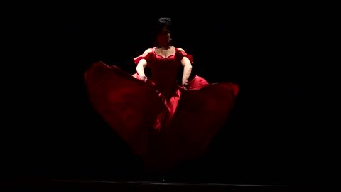 Girl is dancing the sexual movements of a flamenco dance. Black background. Slow motion