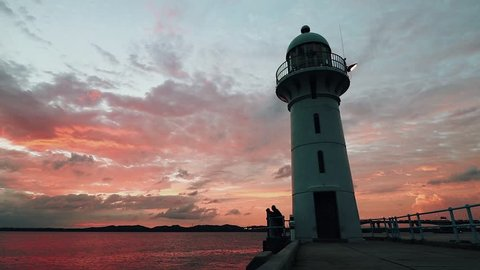 Sunset behind a lighthouse with two men at the base chatting and relaxing