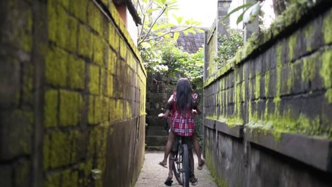 Two children bicycling during golden hour in small alley of Ubud Bali