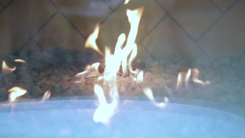 Yellow flames reflect and dance upon upon the glass enclosure of this industrial fireplace. Look closely and you will see the reflections in the glass of nearby patrons.