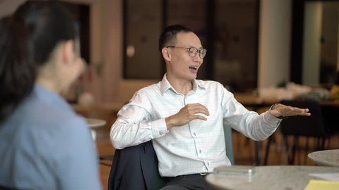 A Chinese Asian business man is sitting and explaining a concept animatedly as he smiles to his team in the office. He is professionally dressed in shirt and pants and looks competent and mature.