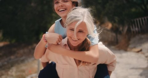 Grandmother and teenage granddaughter having fun with piggyback ride on summer holidays in Mediterranean village