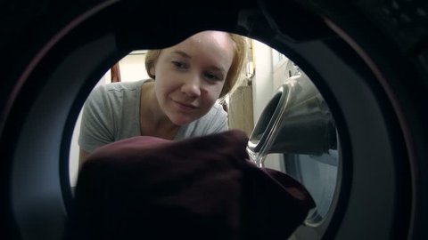 Young Caucasian Woman Loading Dirty Clothes into Washing Machine. Household Chores and Duties Concept.View from Inside