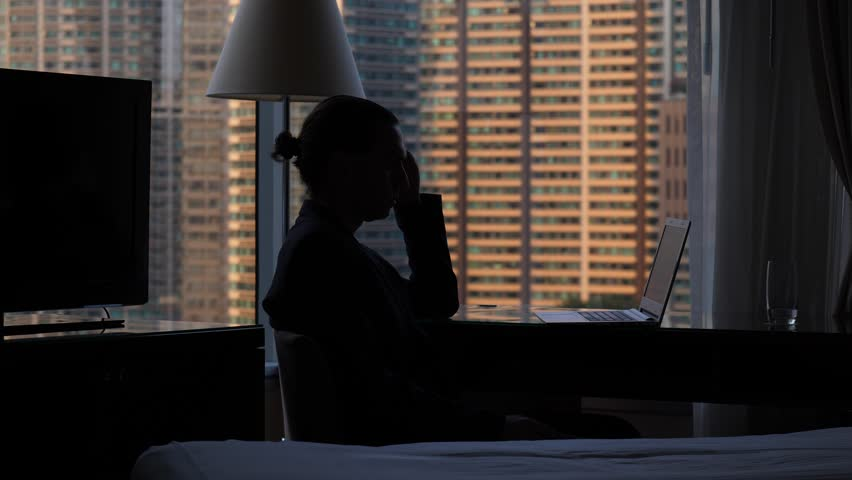 Black silhouette of laptop user sitting at desk against window, half length shot. Man hold head near face and right hand on touchpad of notebook computer, reading some page in internet browser.   Shutterstock HD Video #1013598071