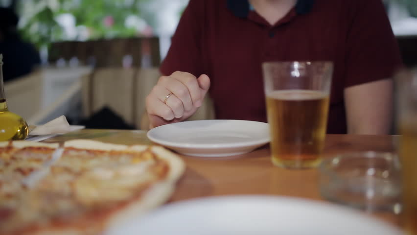 A young man sitting with a friend in a pizzeria drinking beer clinking glasses. Communication after a working day | Shutterstock HD Video #1013613821
